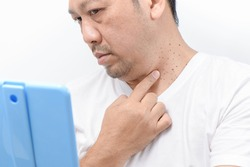 Middle-aged mam point to Skin Tags or Acrochordon on neck man on white background. Health care concept