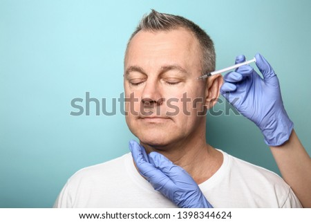 Middle-aged man and hands holding syringe for anti-aging injections on color background