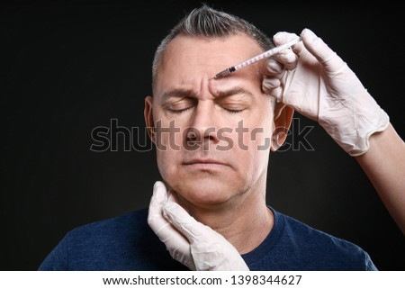 Middle-aged man and hands holding syringe for anti-aging injections on dark background