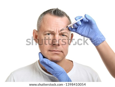 Middle-aged man and hands holding syringe for anti-aging injections on white background
