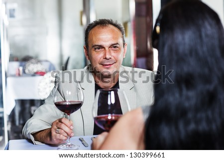 Middle aged man and his wife having romantic dinner in a restaurant