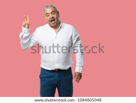 Middle aged man fun and happy, positive and natural, makes a gesture of victory, peace concept