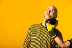 Middle aged man getting punched in the jaw. Hand of a man wearing boxing globes hitting other man in the face against a yellow background