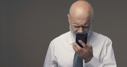 Middle-aged man having difficulties and vision problems using his smartphone, he is unable to read small texts on the screen