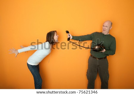 Middle-aged man holds telephone while woman screams at it