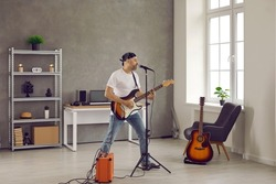 Middle aged man in bandana singing into microphone and playing on electric guitar plugged in AMP. Rock musician playing new music standing in rehearsal room interior with amplifier and other equipment