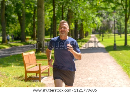 Middle aged man jogging along alley in park on sunny day in a close up view #1121799605