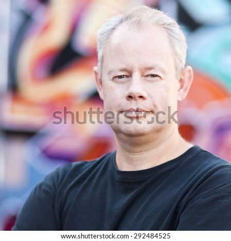 Middle aged man leaning on a graffiti wall in the city
