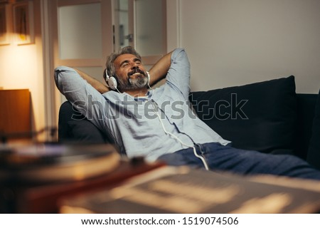 middle aged man listening music at his home