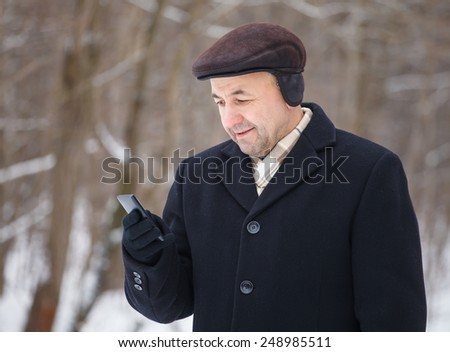 Middle aged man looking at mobile phone in the winter forest