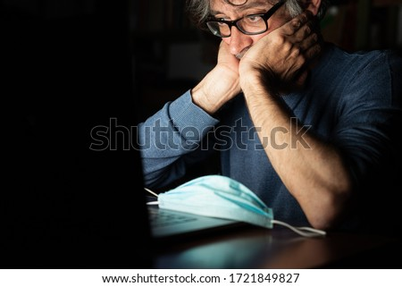 middle-aged man looking on computer at the news about global pandemic from corona virus and he worries, emotional distress, insomnia, concern for business and health in time of covid19 Photo stock ©