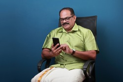 Middle aged man of Indian origin sitting on a chair  checking his mobile phone
