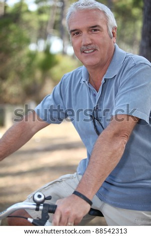 Middle-aged man on bike ride - stock photo