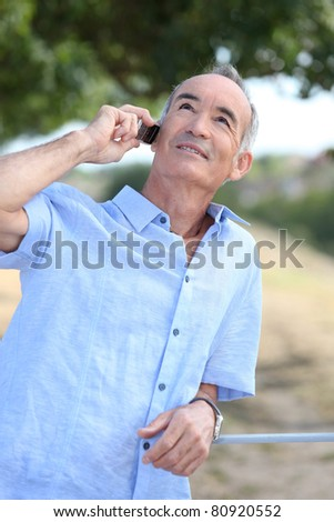 Middle-aged man outdoors with mobile telephone