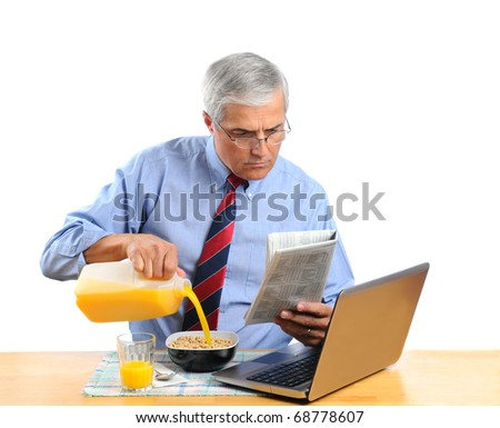 Middle aged man pouring Orange Juice into his breakfast cereal bowl instead of milk . He is in front of his laptop computer reading the morning newspaper. Horizontal format isolated over white.