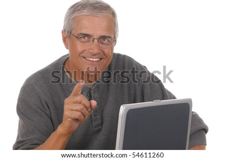 Middle aged man sitting at laptop computer and pointing at camera. Man is smiling and casually dressed. Horizontal format isolated on white.
