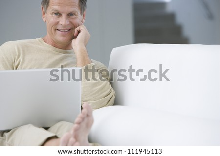 Middle aged man sitting on couch while telephoning