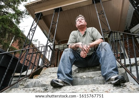 Middle aged man sitting on the steps of a house in the inner city, focus on face Stockfoto ©