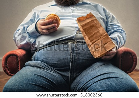 middle aged man snacking in an armchair