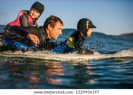 Middle aged man surfing with his two young daughters. #1329456197