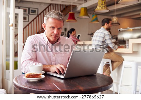 Middle aged man using laptop in a cafe