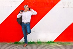 middle aged man using mobile phone on the wall
