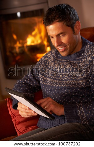 Middle Aged Man Using Tablet Computer By Cosy Log Fire