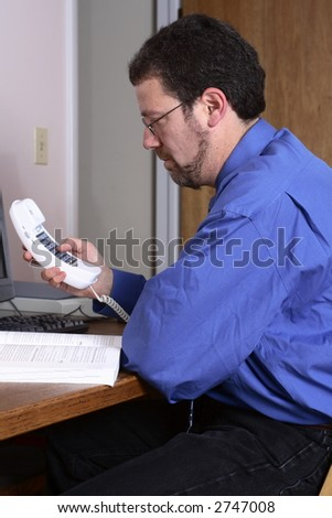 Middle-aged man using the telephone in a home office.