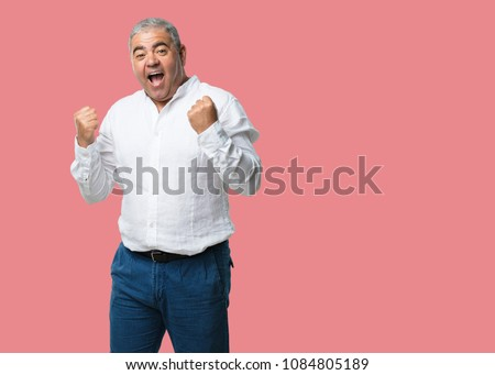 Middle aged man very happy and excited, raising arms, celebrating a victory or success, winning the lottery