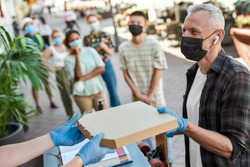 Middle aged man wearing mask and protective gloves receiving pizza from hands of shop assistant while collecting his order from the pickup point during coronavirus lockdown. Horizontal shot