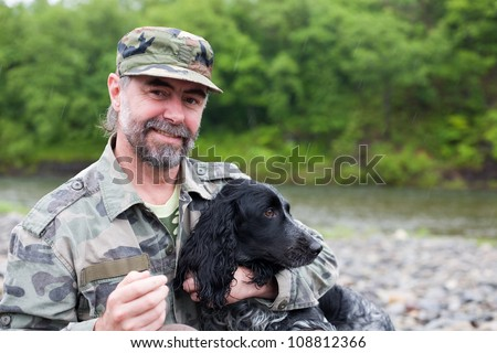 Middle aged man with a dog (Russian Hunting Spaniel). At the river. Rain.