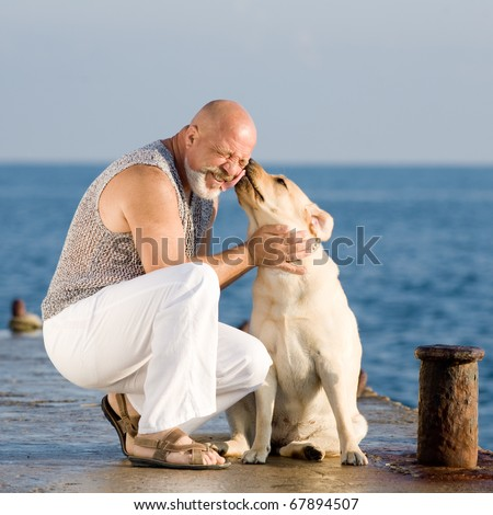 Middle-aged man with Labrador female dog on the coast of the sea