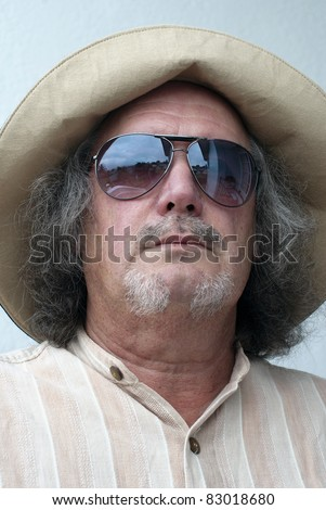 Middle-aged man with long hair, beard, wide hat and sunglasses