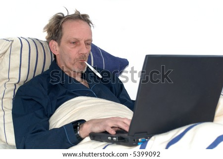 Middle aged man, workaholic, sick in bed working on laptop, thermometer on mouth, feverish. - stock photo