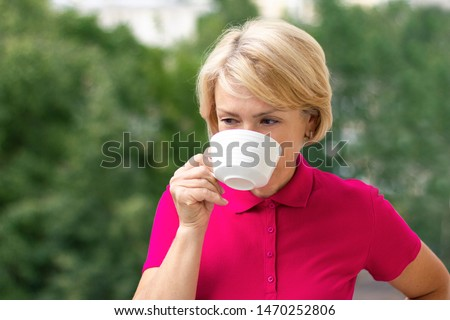Middle-aged mature senior woman is drinking tea or coffee outdoor in a sunny summer day in a pink or red polo shirt. Thoughtful female pensioner holding a mug. Relaxing and thinking, happy retirement.