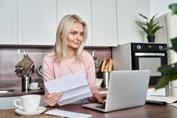 Middle aged mature woman holding paper bill or letter using laptop computer at home for making online payments on website, calculating financial taxes fee cost, reviewing bank account, loan rates.