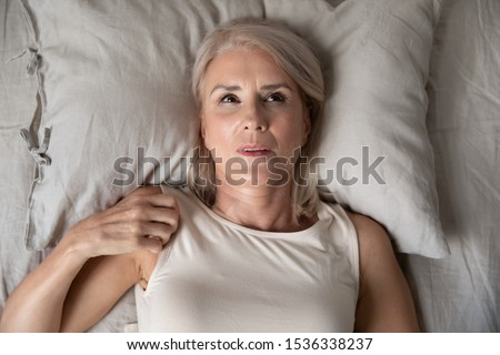Middle aged mature woman insomniac lying awake in bed looking up trying to sleep, unhappy old senior lady feel disturbed frustrated suffer from insomnia concept uncomfortable bad mattress, top view