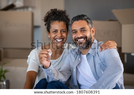 Middle aged multiethnic couple embracing and holding house keys with carboard boxes behind them. Portrait of indian man and african woman showing house keys while looking at camera after relocation. Сток-фото ©