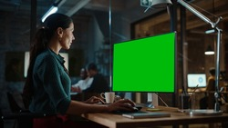 Middle Aged Multiethnic Specialist Working on Desktop Computer with Green Screen Mock Up Display in Busy Creative Office. Beautiful Diverse Female Manager in Green Polka Dot Blouse.