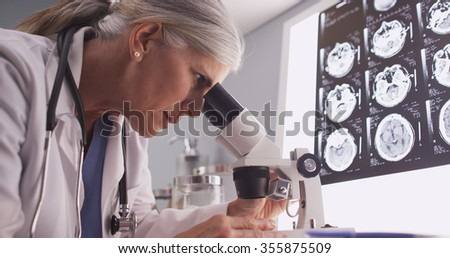 Middle aged neurologist female researching with microscope