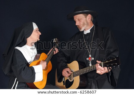 Middle aged nun and priest playing the guitar. Both singing out loud a song, intense expression on face