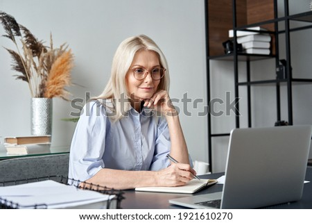 Middle aged older business woman watching professional training class, online webinar on laptop computer remote working, distance learning from home office, conference calling in virtual chat meeting.