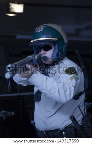 Middle aged policeman aiming rifle while standing in front of car