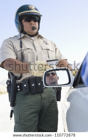 Middle aged policeman checking driving license