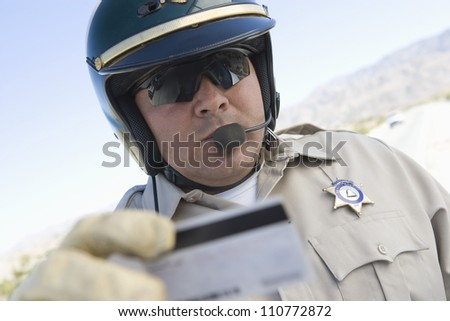 Middle aged policeman checking license