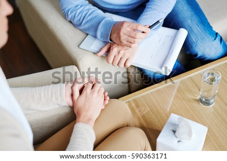 Middle-aged psychologist sitting next to his patient and listening to her childhood story in order to find reason of her disease