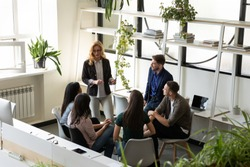 Middle-aged 60s female boss talk with interns gives tasks, teaching young specialists share experience and skills. Diverse colleagues brainstorm in co-working, informal briefing, cooperation concept