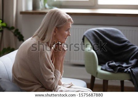 Middle-aged 50s hunched woman seated on couch at home feels upset thinking. Concept of older generation chronic diseases, widow female goes through death of husband, dementia mental disorder concept