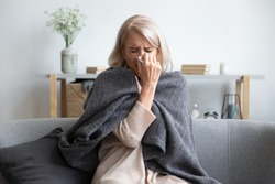 Middle-aged 50s sick frozen woman seated on sofa in living room covered with warm plaid sneezing holding paper napkin blow out runny nose feels unhealthy, seasonal cold, weakened immune system concept