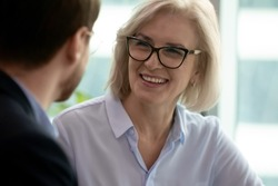 Middle-aged 60s smiling businesswoman talking with partner having pleasant conversation close up focus on female. Negotiations process between client and company manager, mature mentor couch portrait